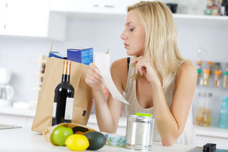 woman checking shopping bag with food