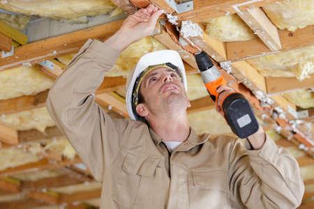 a man installing a ceiling