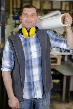 man in factory holding roll of film on his shoulder