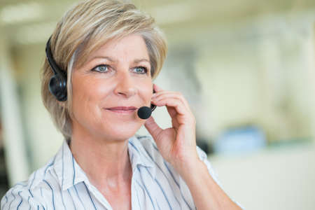 mature female customer-services worker wearing headset Archivio Fotografico