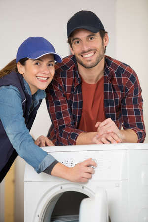 male and female service agents by a washing machine