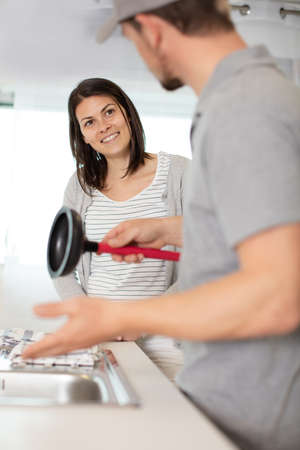 happy woman looking at plumber using plunger in the sink