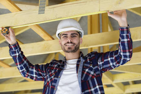 happy male carpenter working on beams