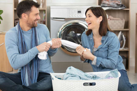 young couple of lovers ahaving fun doing laundry