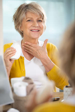 senior woman applying moisturizer to her neck