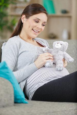 pregnant woman with toy teddy bear 免版税图像