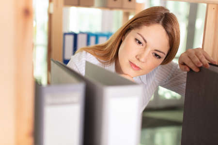 young happy businesswoman searching file in office