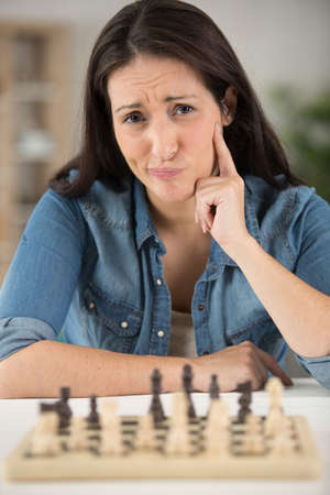 businesswoman is sitting in front of the chessboard