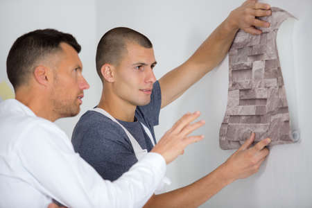 painting apprentice observing wallpaper against a wall