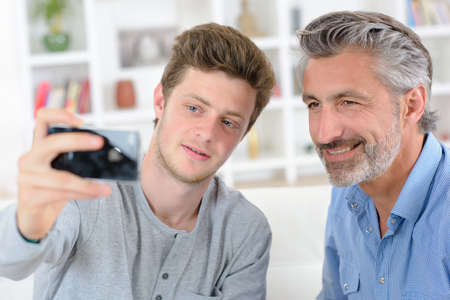 son and father taking selfie