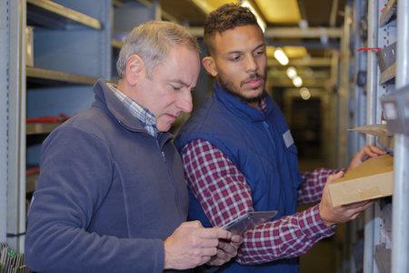 men checking goods in warehouse Banco de Imagens
