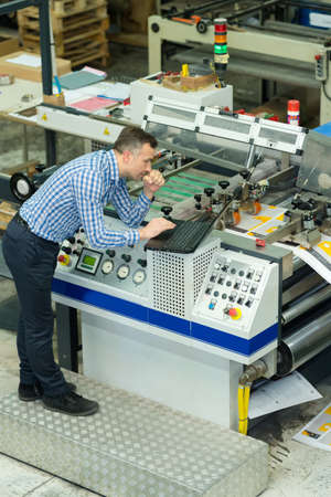 printing press company manager using laptop