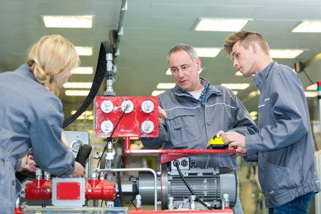 young machine operator inspecting the machine Foto de archivo