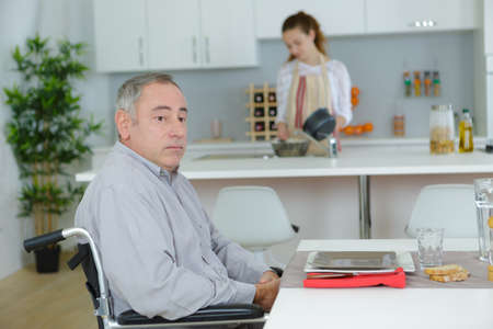 man in wheelchair and young assistant helping