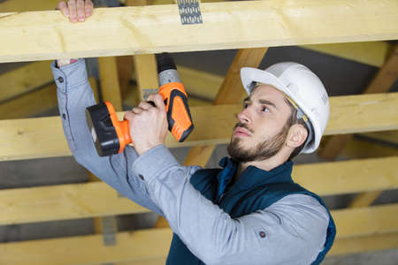 man drilling a wooden frame house