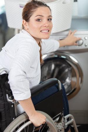 disable woman doing a washing machine