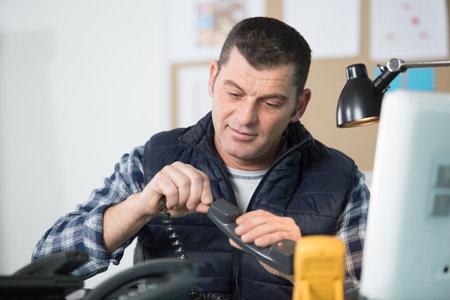 elctrician repair a phone in his workshop