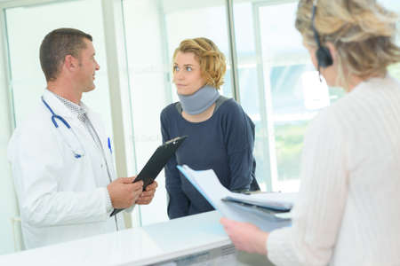 Woman wearing neck support at hospital reception desk