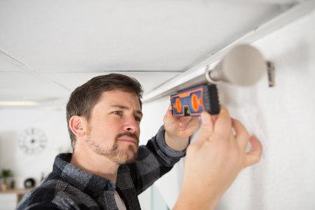 man hanging window curtain indoors