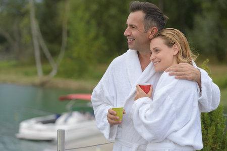 couple in bathrobe sitting on a pontoon