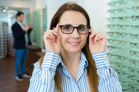 young attractive woman trying glasses at the optician
