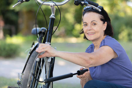 senior woman a bicycle pump to inflate air