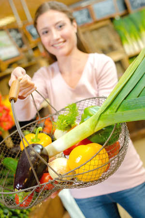 a woman is holding vegetables Stock fotó