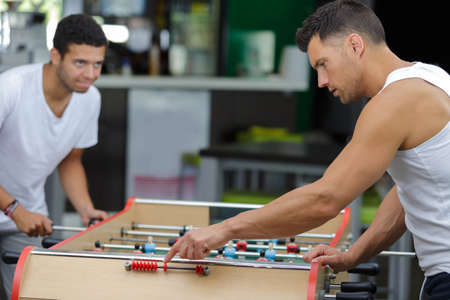 two sportmen playing football table