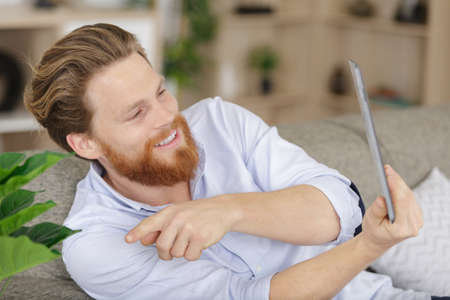laughing man using tablet at home