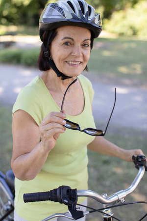 active mature woman with a bicycle 스톡 콘텐츠