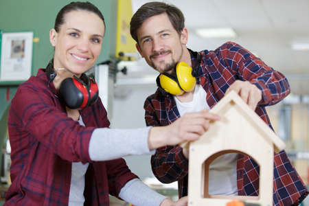 happy workers doing a wood model