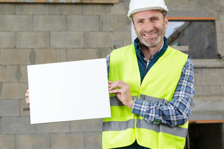 builder man holding a white blank banner Stock Photo