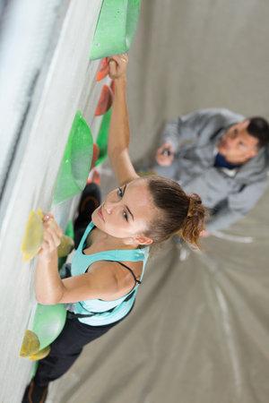portrait of woman climbing a wall Zdjęcie Seryjne