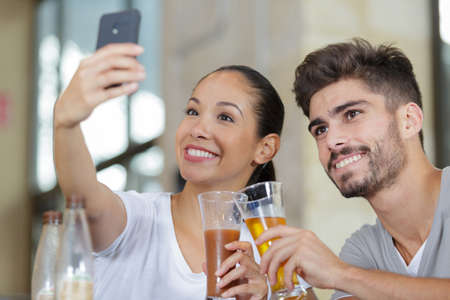 couple at cafe bar making selfie with smart phone