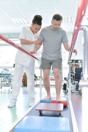man assisted by nurse in rehab clinic 免版税图像