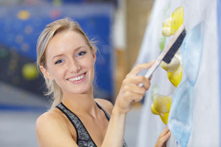 happy young woman cleaning climbing wall