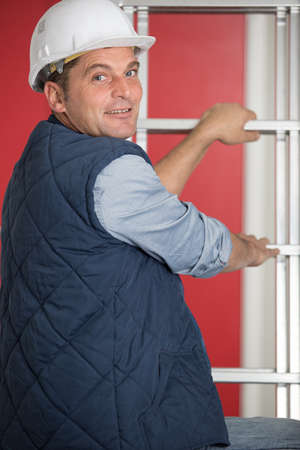 construction worker in helmet climbing a ladder Zdjęcie Seryjne