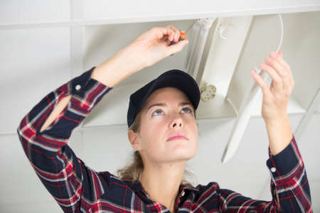 female building electrician investigating the problem