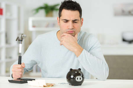 sad student breaking piggybank to pay for tuition fees