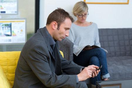 man using a phone while waiting