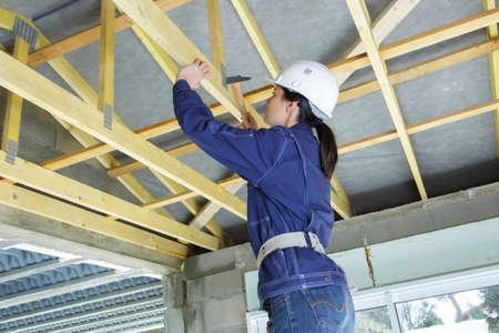 female carpenter hammering wooden structure Banque d'images
