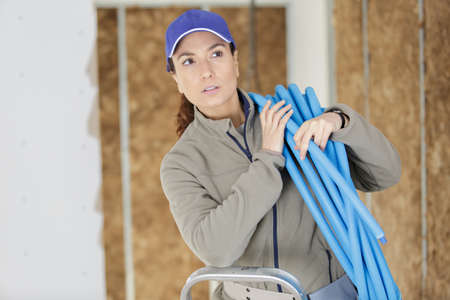 female elctrician fitting air conditions pipe in building ceiling