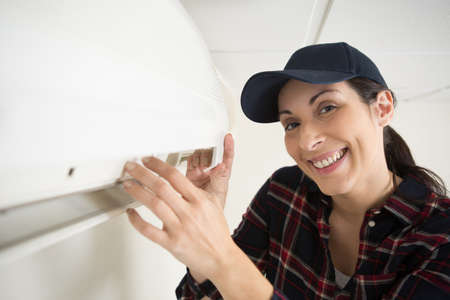 female technician cleaning air conditioner indoors