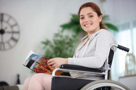 disabled woman sitting in a wheelchair and holding a magazine