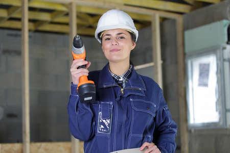 female laborer holding a drilling machine