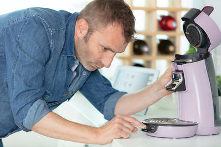 concentrated man renovating coffee machine