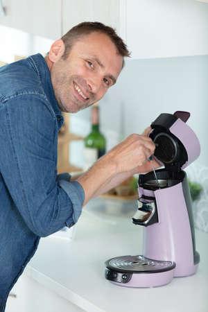 mature man fixing a coffee machine