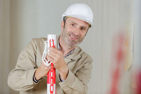 male construction worker erecting safety barrier