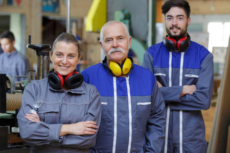 senior foreman with young man and woman in overalls