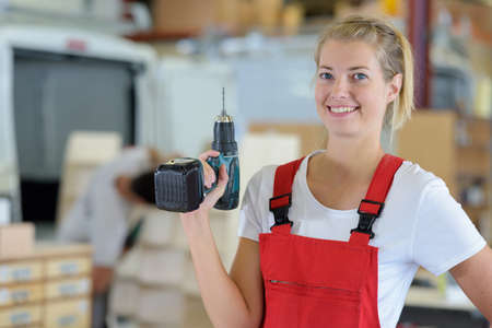 female carpenter posing holding a drill Banque d'images